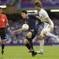 Physical contest: Japan's Kensuke Nagai vies for the ball with Korea's Ki Sung Yueng in the third-place match in Cardiff, Wales, on Friday. Korea won 2-0. | AP