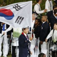 Know your country: Yoon Kyun Shin carries the South Korean flag during Friday night's Opening Ceremony. | AP
