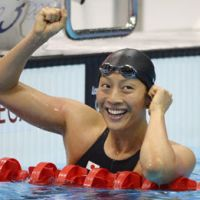 Podium finish: Osaka native Aya Terakawa reacts after taking the bronze medal in the women's 100-meter backstroke on Monday at the Aquatics Centre. | AP