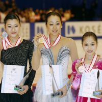National treasure: Runnerup Kanako Murakami (left), champion Mao Asada (center) and bronze-medalist Satoko Miyahara pose with their prizes on Sunday. | KYODO