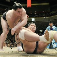 Happy New Year: Harumafuji throws Myogiryu to the ground at the New Year Grand Sumo Tournament on Monday. | KYODO