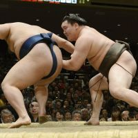 On to the next one: Yokozuna Hakuho (right) forces Goeido out of the raised ring on Tuesday at the New Year Grand Sumo Tournament. | KYODO