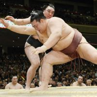 Still going strong: Yokozuna Harumafuji (rear) prevails over ozeki Kisenosato on Friday at the New Year Grand Sumo Tournament. | KYODO
