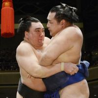 Triumphant: Yokozuna Harumafuji outduels ozeki Kakuryu on the 14th day of the New Year Grand Sumo Tournament on Saturday. Harumafuji (14-0) clinched the Emperor's Cup. | KYODO