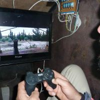 Fighting machine: Syrian rebels stand atop Sham II, a homemade armored vehicle made by the Al-Ansar brigade in Bishqatin, near the city of Aleppo, on Saturday. Right: A fighter uses a PlayStation controller to activate the vehicle's machinegun. | AFP-JIJI