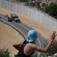 Slings and stones: A Palestinian tries to sling a rock at Israeli soldiers as they patrol the controversial separation barrier built by the Jewish state during clashes near the village of Bilin, west of Ramallah, in April. | AFP-JIJI