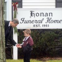 First of too many: A man speaks to a boy Monday at the funeral for Jack Pinto, 6, one of the victims of Friday's Sandy Hook Elementary School massacre in Newtown, Connecticut. Funerals began Monday in the small town after the mass carnage. | AFP-JIJI