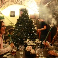 Old World traditions: Syrian women smoke water pipes as a waiter decorates a Christmas tree at a cafe in the old city of Damascus on Thursday. Most in the Christian community in Syria are celebrating Christmas without decorations this year amid the ongoing conflict, but Amer, the owner of the cafe, has decided to carry on the tradition. | AFP-JIJI