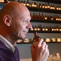 Nose for talent: British perfumer Mark Buxton smells perfume in a bottle at his workshop in Paris. | AFP-JIJI