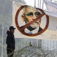 Whose your Badie?: An Egyptian riot soldier stands under a banner of Muslim Brotherhood leader Mohammed Badie near barbed wire at the presidential palace in Cairo on Friday. | AP