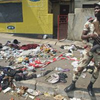Peace celebration turns into tragedy: A soldier stands next to the belongings of people caught up in a deadly stampede in Abidjan that occurred just after a New Year's fireworks display. | AP