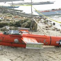 Lost and found: A U.S. drone is shown on a beach in the town of San Jacinto last week after Filipino fishermen found the 3.65-meter device floating off Masbate Island and dragged it ashore. | AFP-JIJI