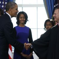 Oath of office: President Barack Obama shakes hands with Chief Justice John Roberts after Obama was officially sworn in for his second term as first lady Michelle Obama and daughters Malia (left) and Sasha watch at the White House in Washington on Sunday. | AP