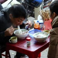 Slurp! Slurp!: People eat 'pho' (noodle soup) in front of a pho restaurant in downtown Hanoi on Jan. 11. In Hanoi, it is universally acknowledged that the best pho can only be found in grimy, spartan restaurants with rude staff. | AFP-JIJI