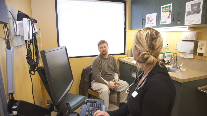 Pioneering spirit: Oregon's plan to slow medical cost growth is 'the triple aim': higher-quality care and better outcomes for a lower cost. Here, Angelina Zamboni consults with patient Michael Boone at Mosaic Medical in Bend, Oregon.