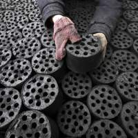 Fuel to the fire: A worker moves briquettes at a coal distribution business in Huaibei, central China, on Wednesday. Experts are warning that a demographic time bomb could scupper the country's breakneck economic growth. | AFP-JIJI