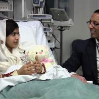 Getting better all the time: Pakistani schoolgirl Malala Yousufzai, who was shot in the head by the Taliban, speaks to a doctor at Queen Elizabeth Hospital in Birmingham, England, in a video grab taken from her first public statement released Monday. | AFP-JIJI