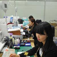 More leisure time: Industrial Bank of Korea employees, shown working in Seoul in the middle of January, can now leave the office at 7 p.m. | AFP-JIJI