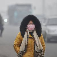 Chemical soup: A woman wears a mask Sunday as she braves the polluted streets of  Tangshan, Hebei Province, China. | KYODO
