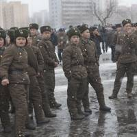 In it together: North Korean soldiers gather on the streets of a snowy Pyongyang on Sunday. | AP