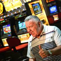 Hitting the slot: Retiree Peter Bell sits among electronic poker machines at Sydney's Randwick Labor Club in December. | AFP-JIJI