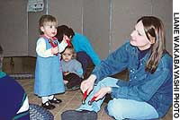 Holding handbells, 18-month Ella Davis takes a confident step toward teacher Karla Watauchi as Kindermusik classmates look on.