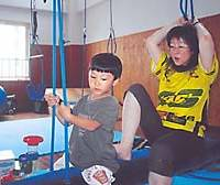 Rio Akiyama tries out the sensory therapy swing with occupational therapist Kayano Wakamatsu at Twirly Melon Island in Okayama.