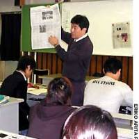 Hideharu Tajima uses English-language newspapers to teach his students at Shinjuku High School.