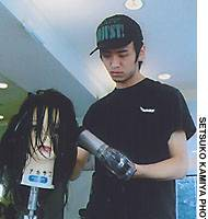 Hiroo Akazawa at Toni & Guy uses a dummy to practice blow-drying hair before the salon opens.
