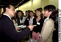 Nissan President Carlos Ghosn makes a point to Chikako Fujie, one of a group of Nissan-NPO Learning Scholarship Program recipients at a Nissan Investment in the Future Society reception at the company's Tokyo head office last June.