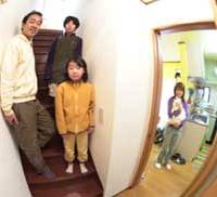 Shuji and Takako (left and right) in the two-story home they made by installing a kitchen, living room and bathroom on the first floor they had rented out, with four rooms upstairs in their former apartment.