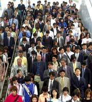 Workers exit a Tokyo station during the morning rush hour. (Yoshiaki Miura Photo)
