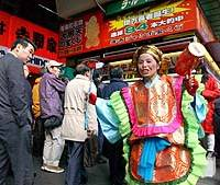 A lottery campaign woman in Daikokuten costume at a booth in Tokyo's Yurakucho Station.