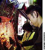 A lottery player prays for luck to a statue of Daikokuten, a god of prosperity.
