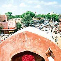 A plasterer works on the Chandpol Gate overlooking Jaipur's bustling streets.