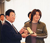 Horie receives his company's certificate of listing on the Mothers market for emerging stocks at Tokyo Stock Exchange in 2000, when he was age 27.
