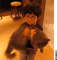 A boy on a visit to Cats Livin carries a new furry friend he has found there.