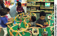 Kids amuse themselves with a large wooden model railway at Hakuhinkan Toy Park in Ginza (Above); kids play remote-controlled robot soccer at Yuzawaya in Kichijoji.