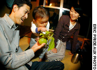 At-home dad Hiroshi Inomata plays with his son Mizuki as wife Mariko, an infant-massage instructor, looks on.