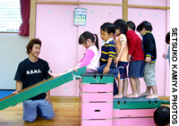 Nursery  teacher Dan Ehara encourages some of his 3-year-old charges at Kamimeguro Nursery in Tokyo's Meguro Ward to enjoy themselves while also getting planned exercise.