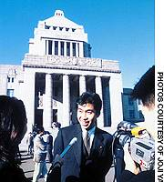 Joji Yamamoto, then a rising star in the Democratic Party of Japan, is interviewed by the media outside the Diet building in Tokyo's Nagatacho district in 1996 on his first day as a newly sworn-in member of the House of Representatives.