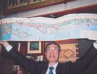 Kimio Koketsu of Ohya Shobo holds aloft an 1860 woodblock print of the Tokaido Highway by Gountei Sadahide.
