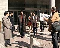Education board 'minders' (left) and supporters (right) meet Tokyo teachers leaving an enforced 'study course.'