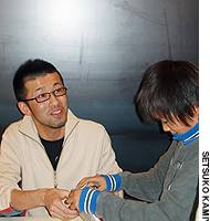 Tomohiro Yasui greets a 10-year-old boy who brought a 'Kami-Robo' character he made to show him at last month's 'Kami-Robo Expo 2005' held in Tokyo.
