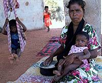 A woman sits with her children in the shade of a refugee camp in the eastern province of Trincomalee.