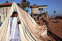 A young couple sets up a tent in front of their battered family home in the southern town of Hambantota.
