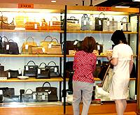 Shoppers at the Komehyo 'super discount recycle department store' in Osu eye brand bags.