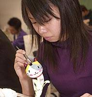A student paints her elegant version of a manekineko