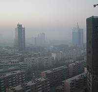 The oil-boom skyscrapers tower over tenement housing for Uighurs.