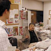 Nikkei Trendy's Editor-in-Chief Mori Kiramura briefs his staff from behind his desk weighed down with test reports and product specifications.